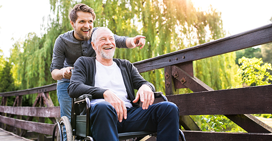 younger man pushing an older man in a wheelchair