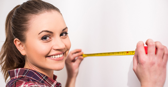 smiling woman holding measuring tape up to wall