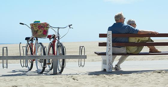 senior man and woman on bench next to bikes at beach