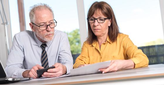 man and woman looking at financials