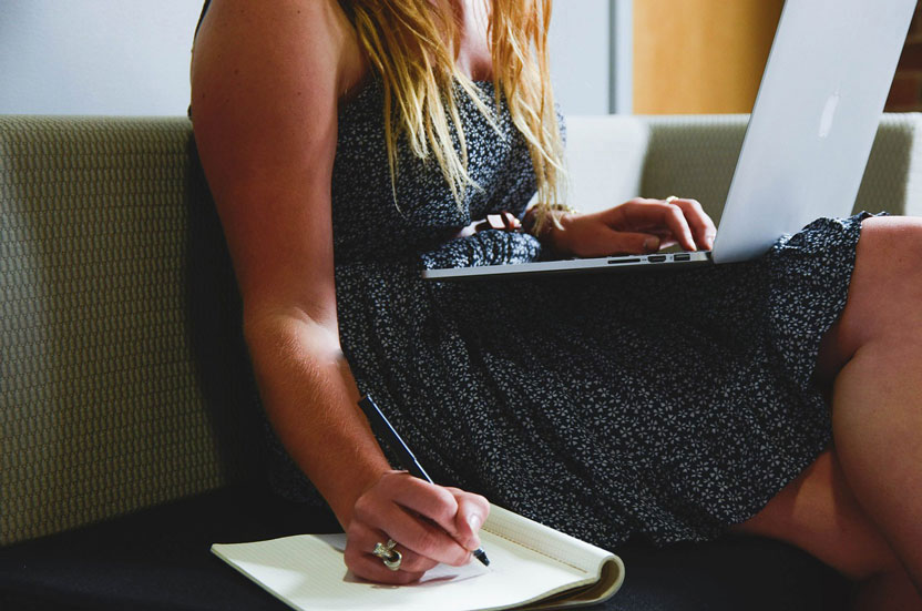 woman on laptop making list