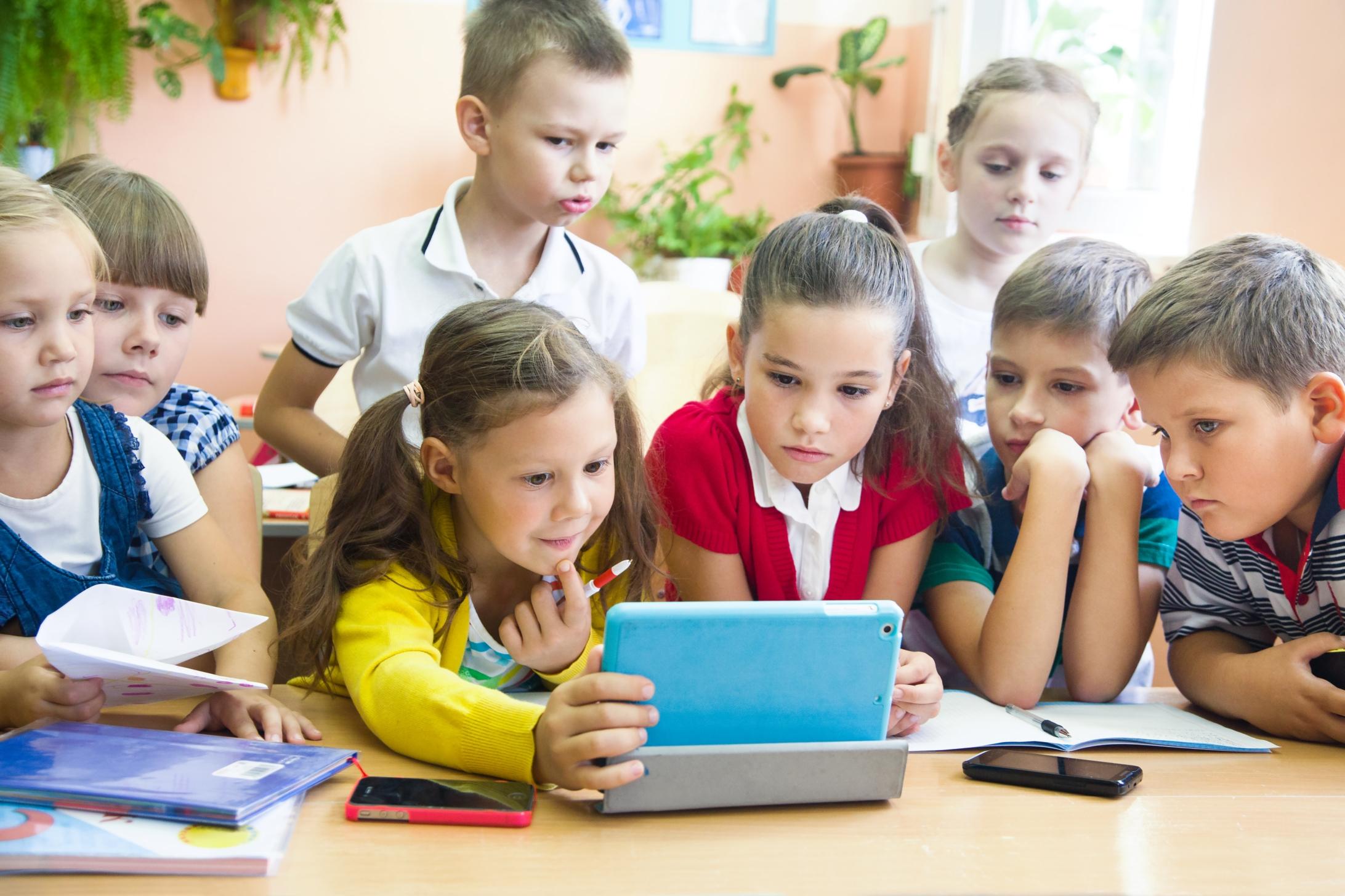 Des enfants regardent attentivement une tablette dans une salle de classe.