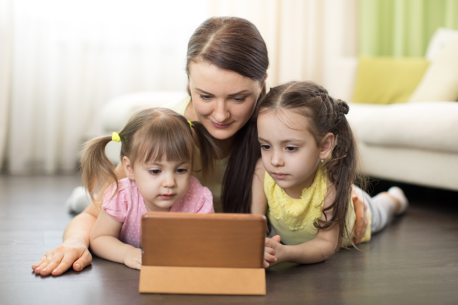 Une maman qui regarde une tablette avec ses deux filles. A mother looking at a tablet with her two daughters.