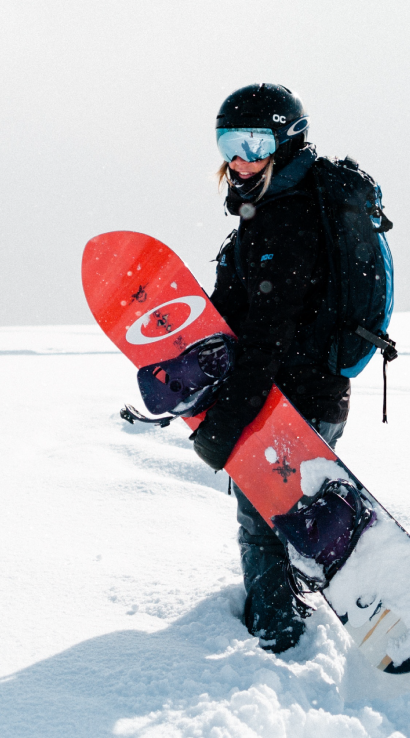 Snowboarder standing in snow with quality used sports equipment