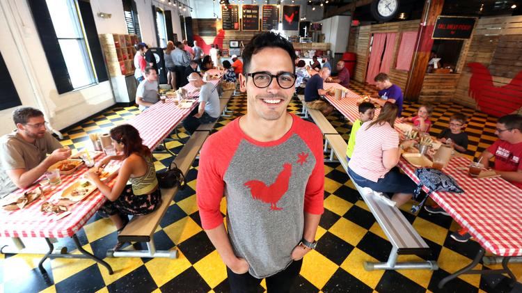 Hot Chicken Takeover owner Joe DeLoss standing and smiling in resaurant