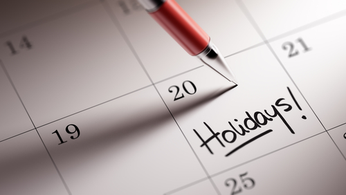 "pen on a calendar that reads ""holidays"""