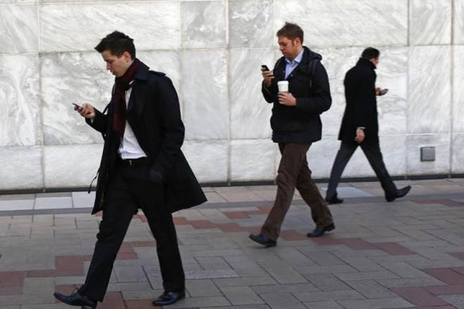men in suits walking while looking down at phone
