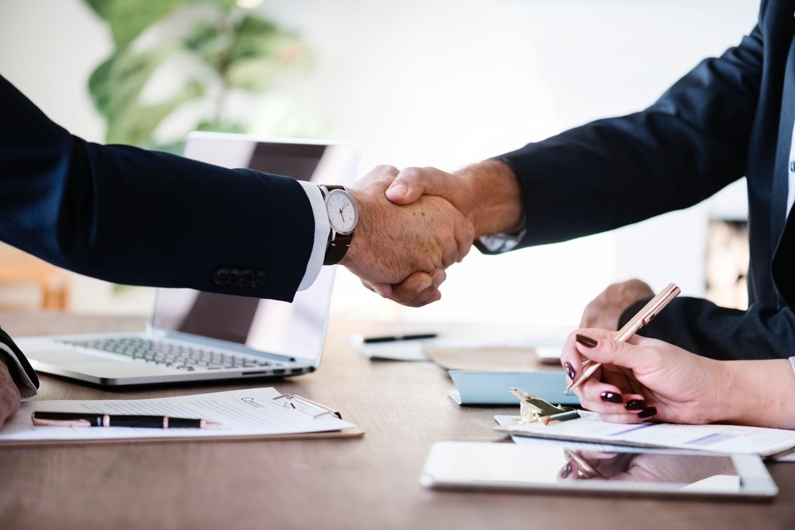 men with paperwork in suits shake hands
