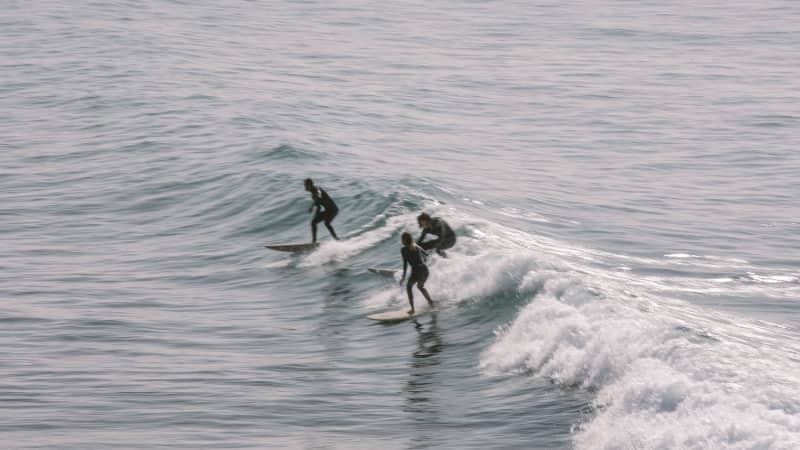 three surfers riding a wave in morocco