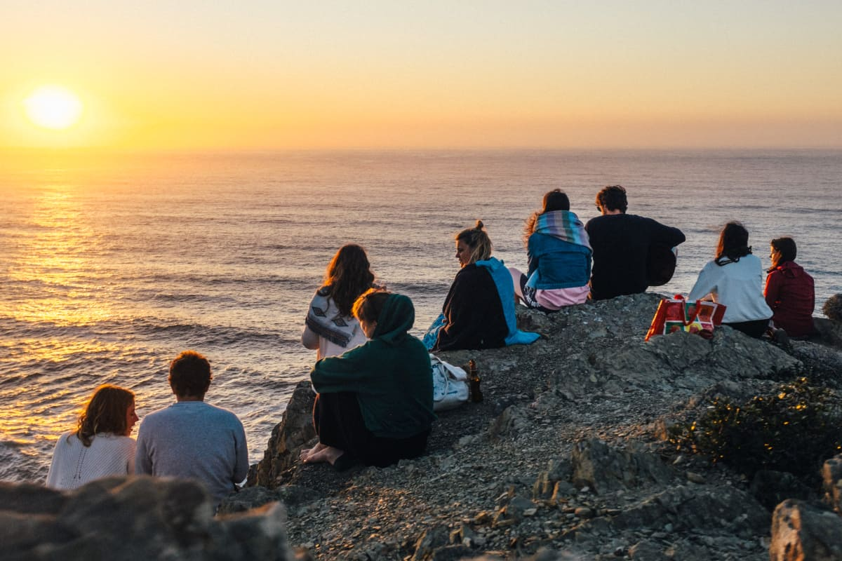 the surf tribe group of friends at sunset on a cliff
