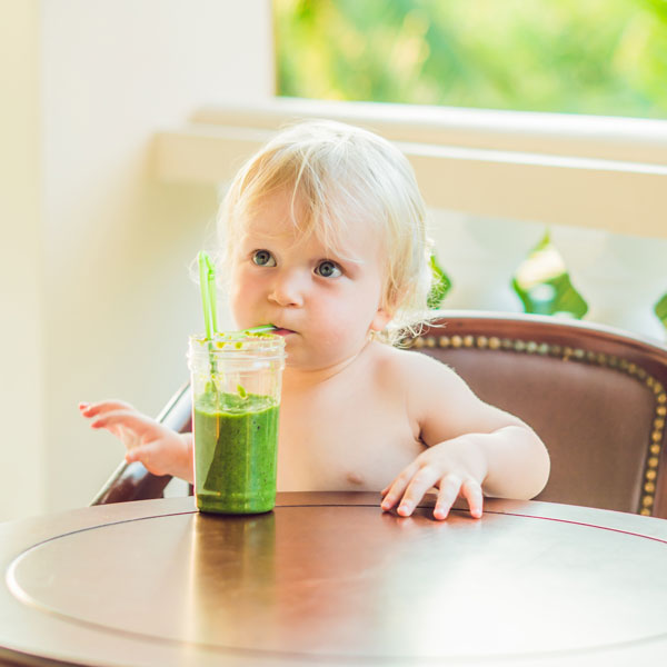 Baby drinking a green smoothie