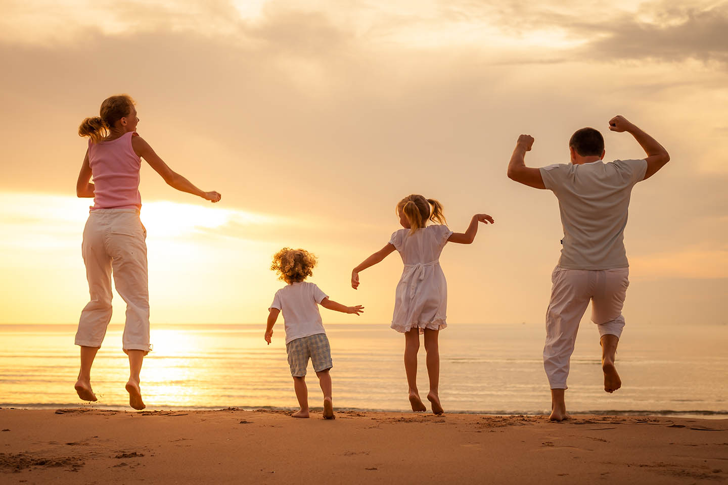 Family of four jumping on the beach at sunset