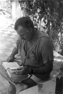 """EH 3963 Ernest Hemingway reading outside at Finca Vigia in Cuba. Please credit """"Ernest Hemingway Collection/John F. Kennedy Presidential Library and Museum, Boston"""""""