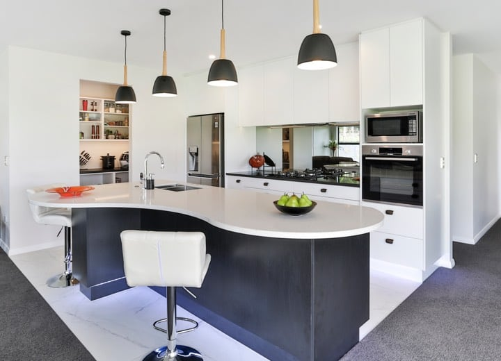White kitchen with curved island and bar seating