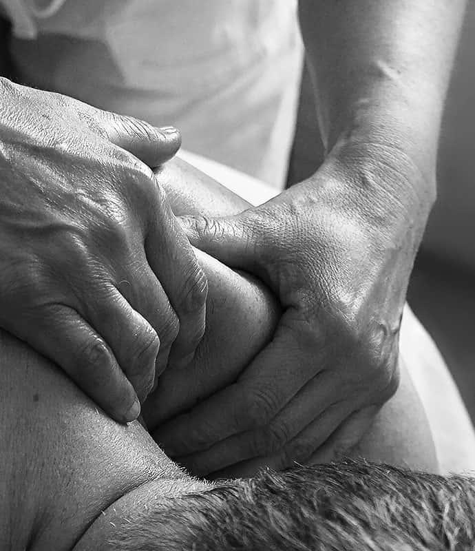 Des mains massant le haut du dos d'un homme.