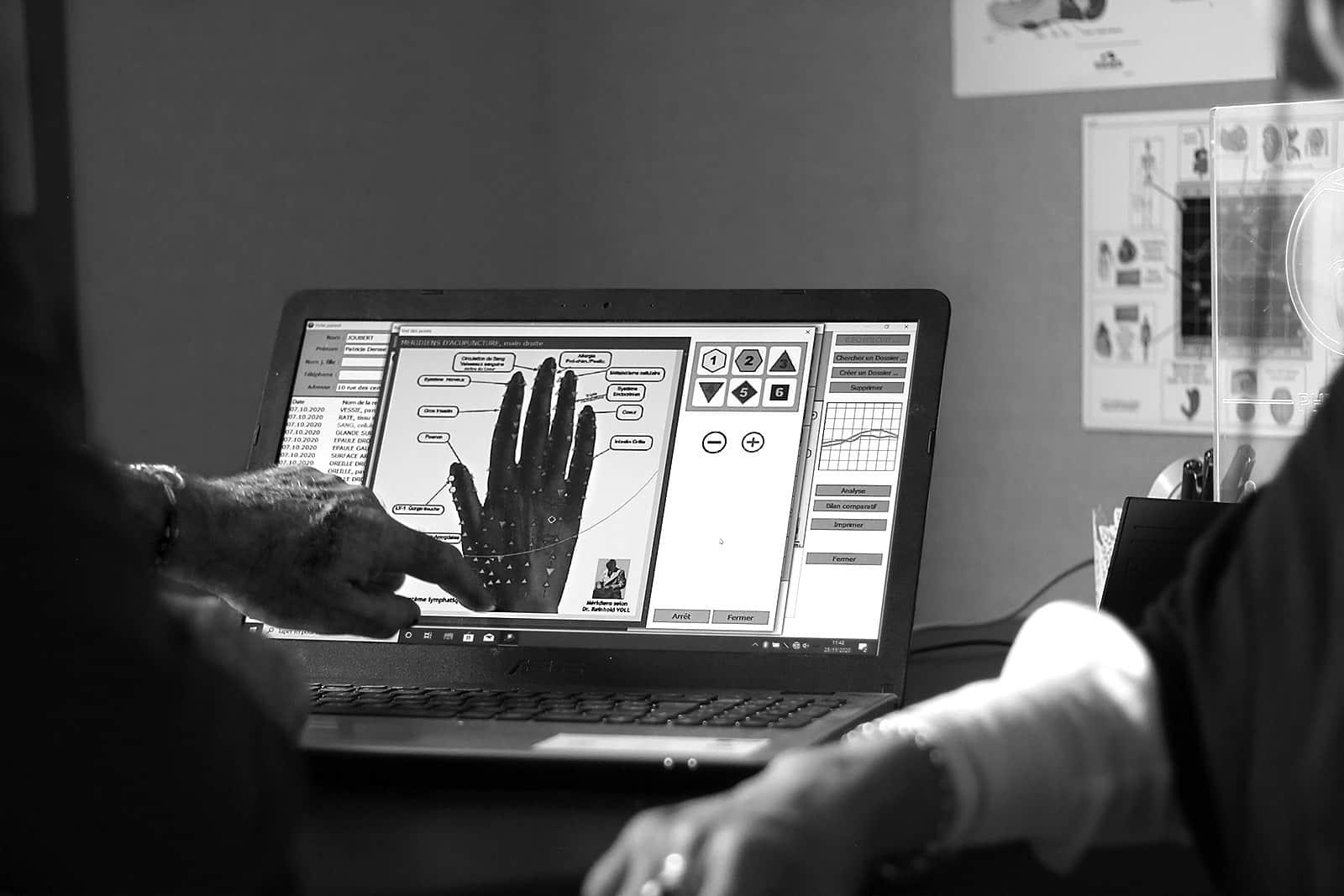 Didier Martin, du cabinet Tangan, donne une séance de Physioscan. Il montre des résultats sur l'ordinateur.