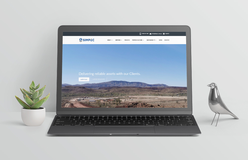 simpec website mockup on laptop with plant and bird items