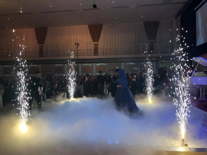 Een paar dansen in het midden van het podium met een vuurwerk- en rookshow.