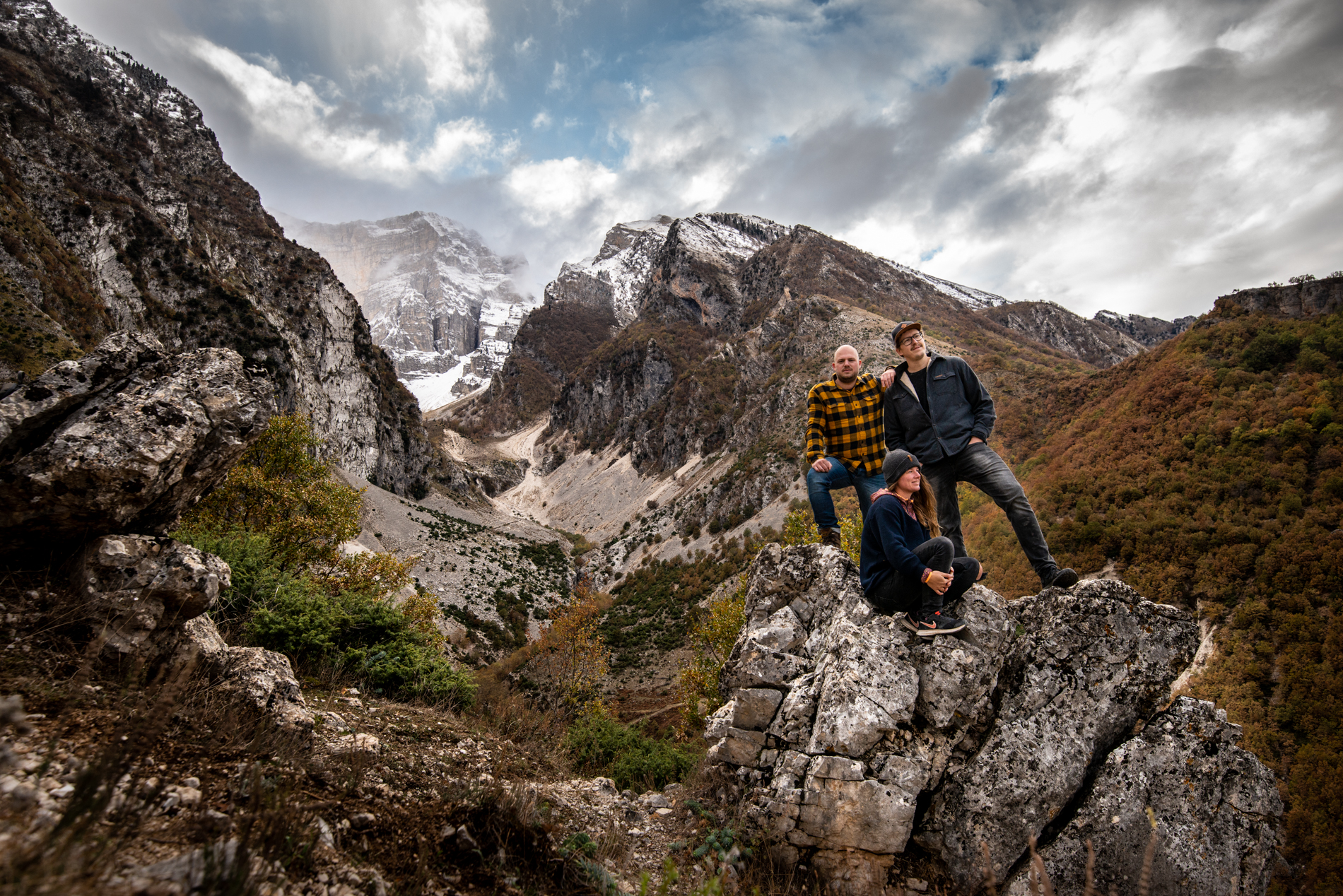 Band photo of Ellisandme and their friend, posing on a rock with snow mountains on the back. Përmet Gjirokäster, Albania.