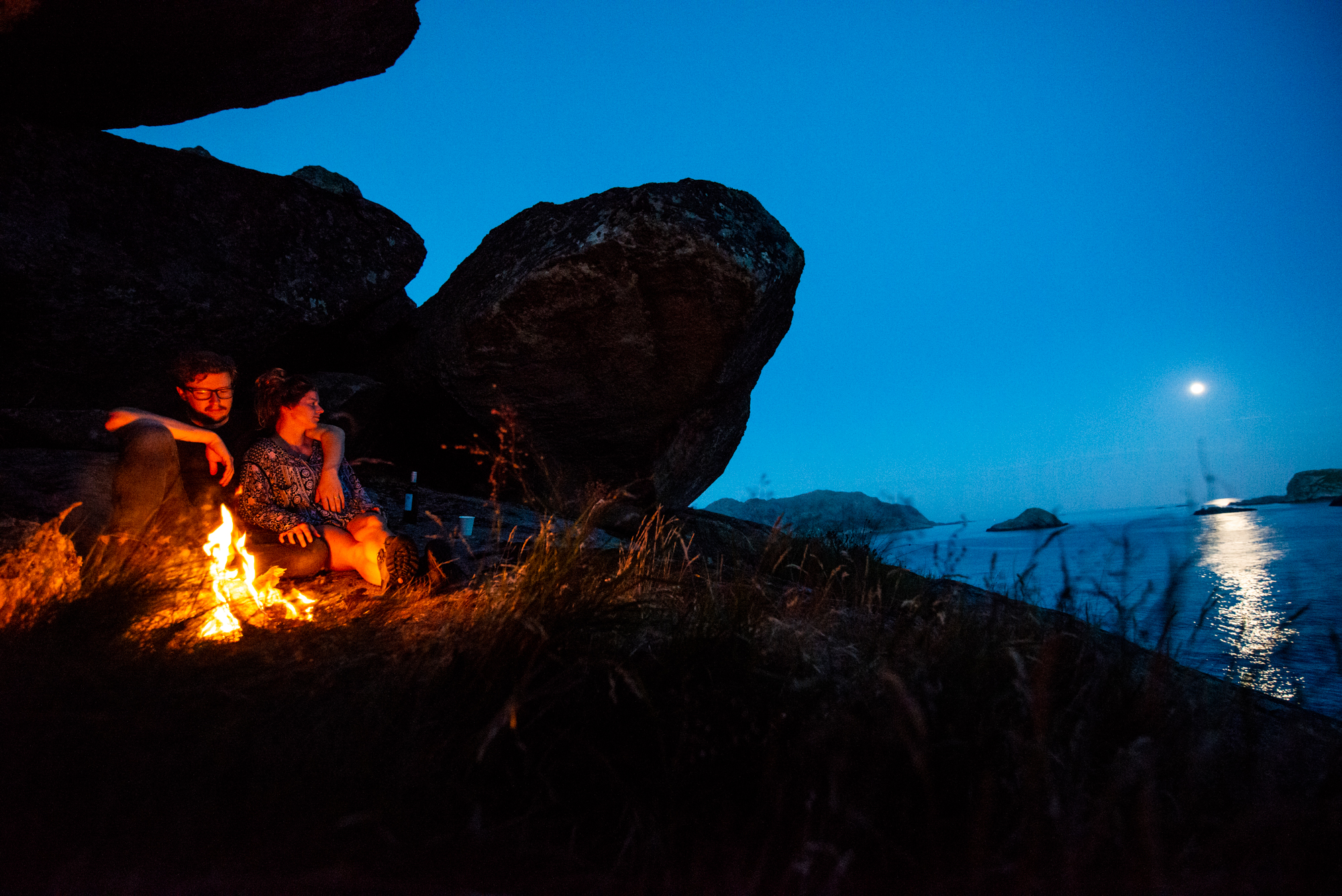 Ellisandme camping at a cave close to the ocean with a fire and a full moon reflecting on the sea. Norway.