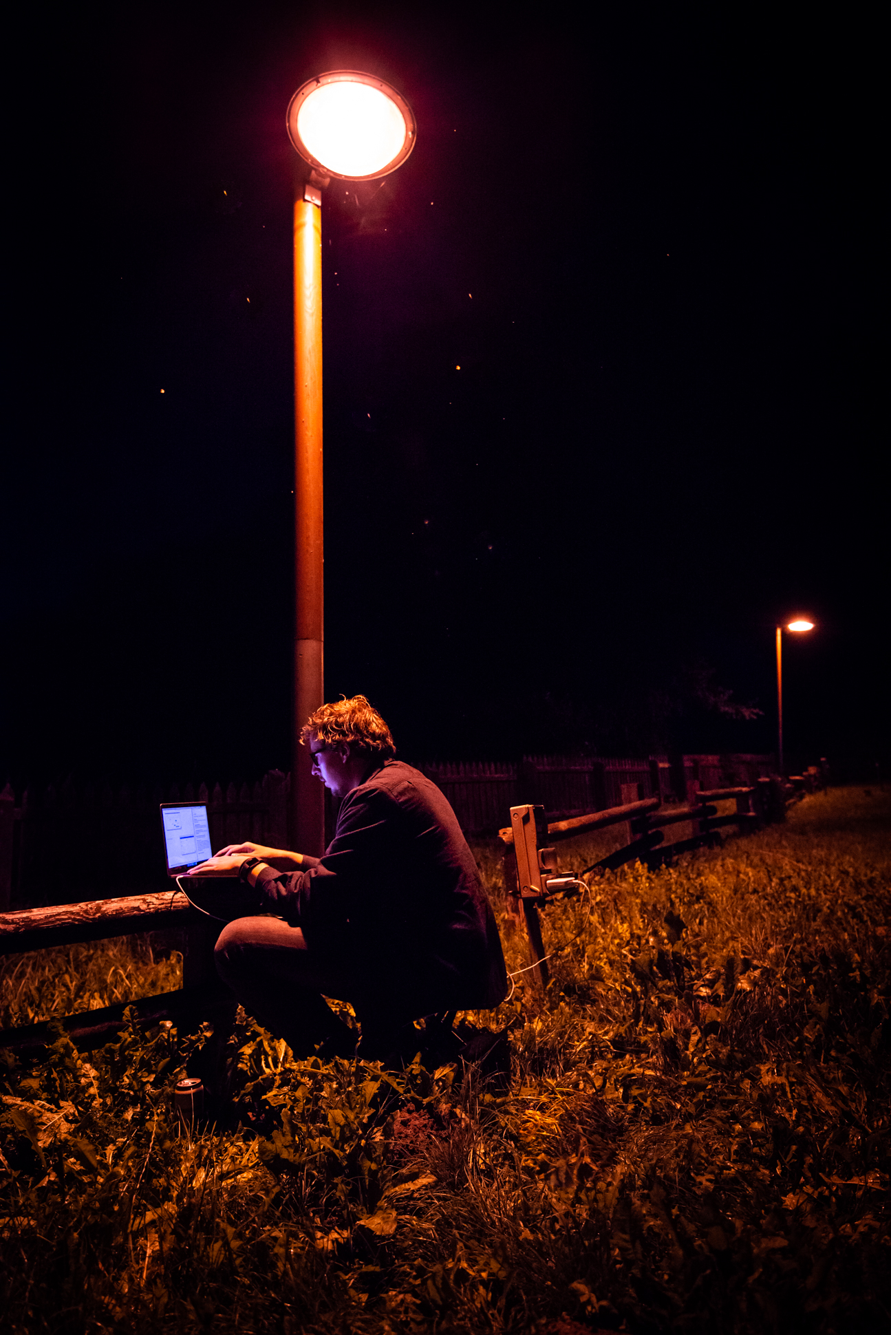 Digital Nomad working at a camping in Kurtuvenai in night time, under a lamppost, Lithuania. Ellis&me Ellis Photography.