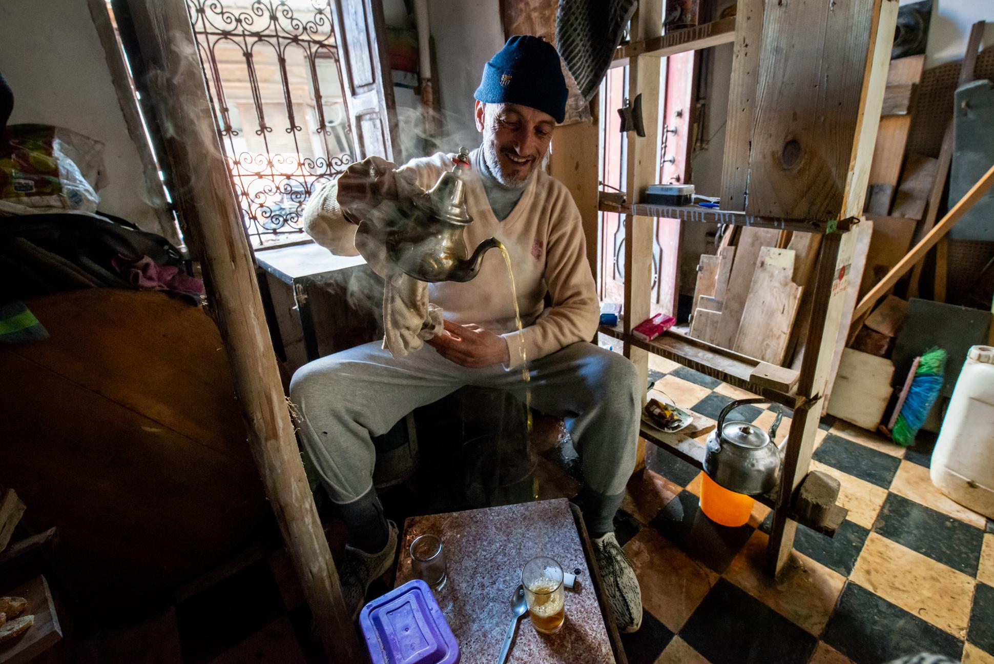 Moroccon man making Moroccon whisky, sweet mint tea. Environmental portrait by Ellis & Me.