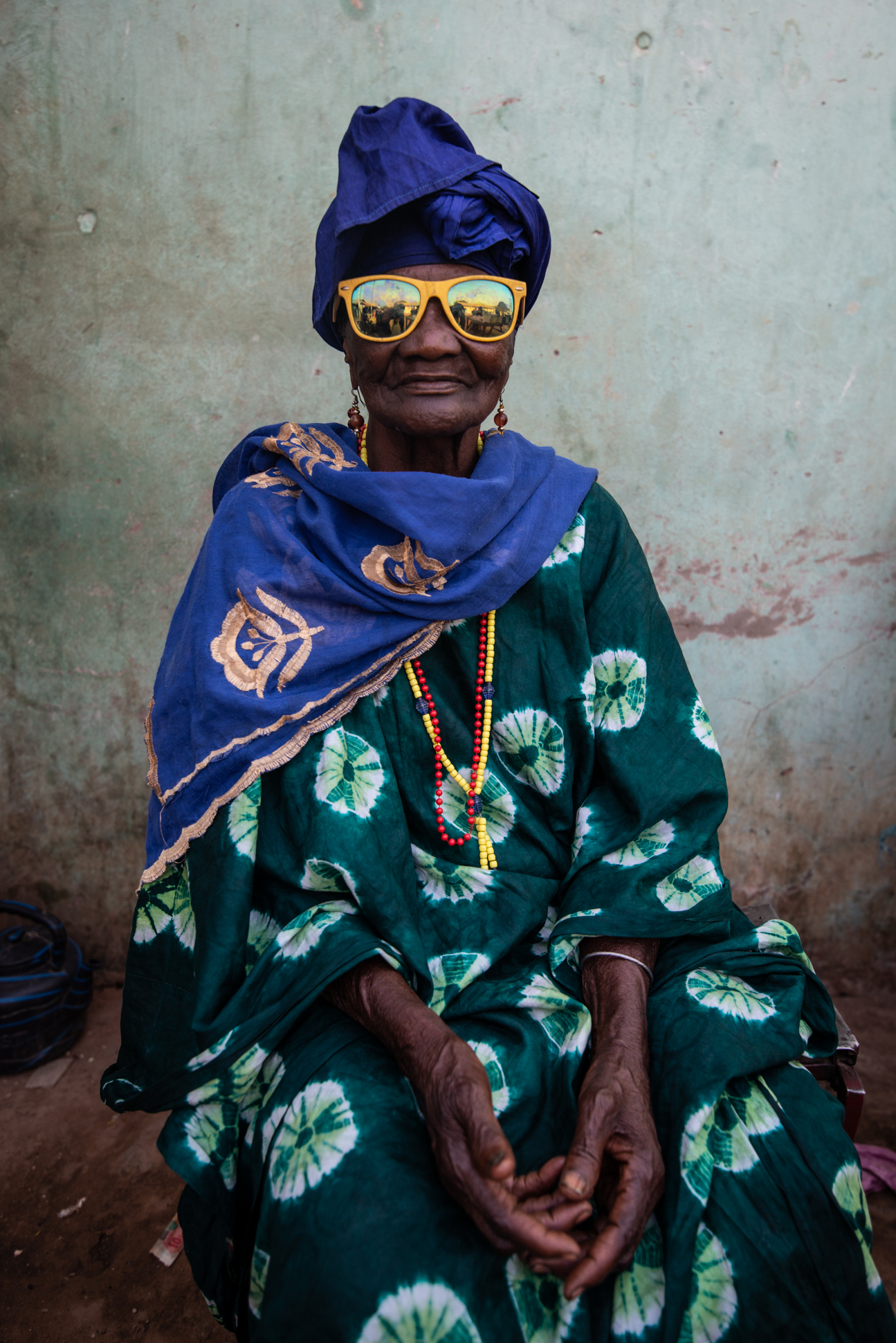 Portrait of an old lady wearing yellow sunglasses in Gunjur, the Gambia. Portraitphotography by Ellis photography.