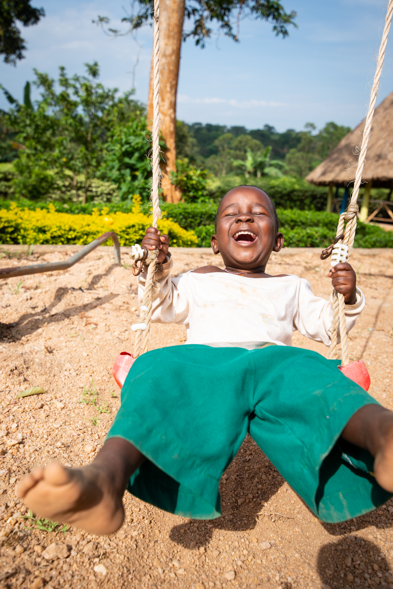 Portrait of an orphanage boy on a swing with a big smile. Ellis and me in Uganda.
