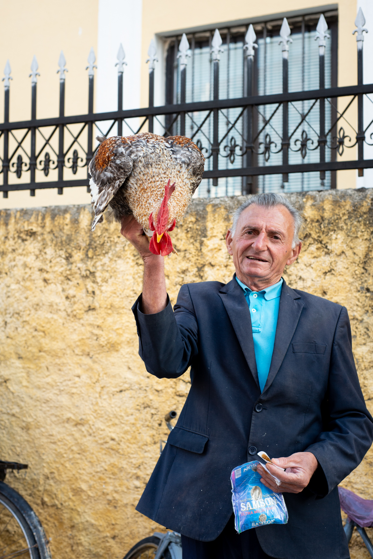 Albanian man holding a cock, rooster. Ellis photography