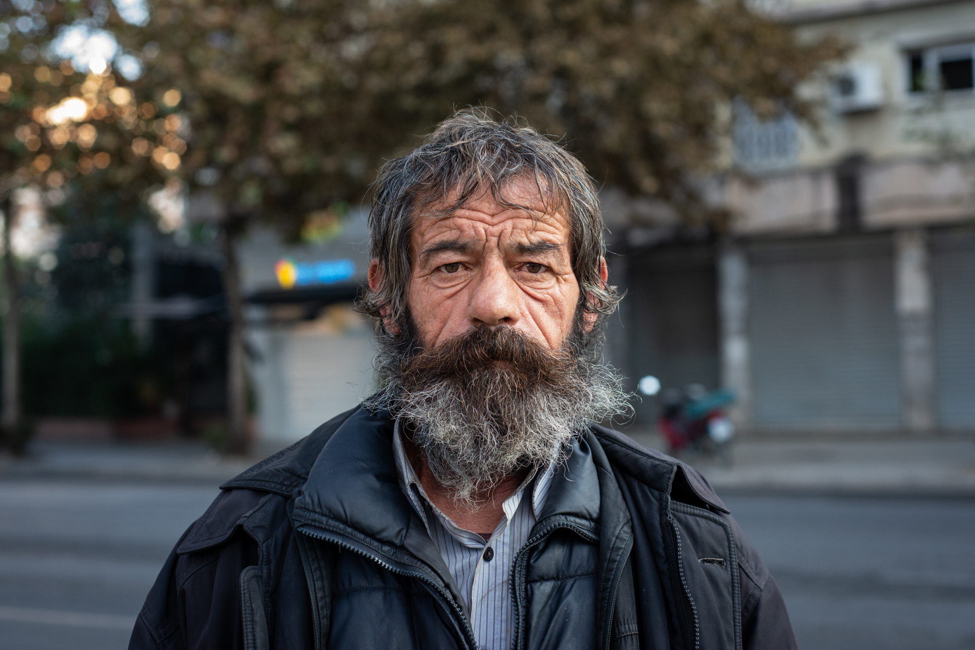 Man of the streets. Portrait of a homeless with a gray long beard. Ellis Photography.