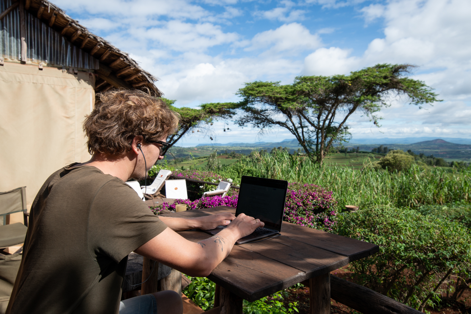 Digital nomads at Rhotia valley in Tanzania. Great view with bleu sky, white clouds, green trees and hills.