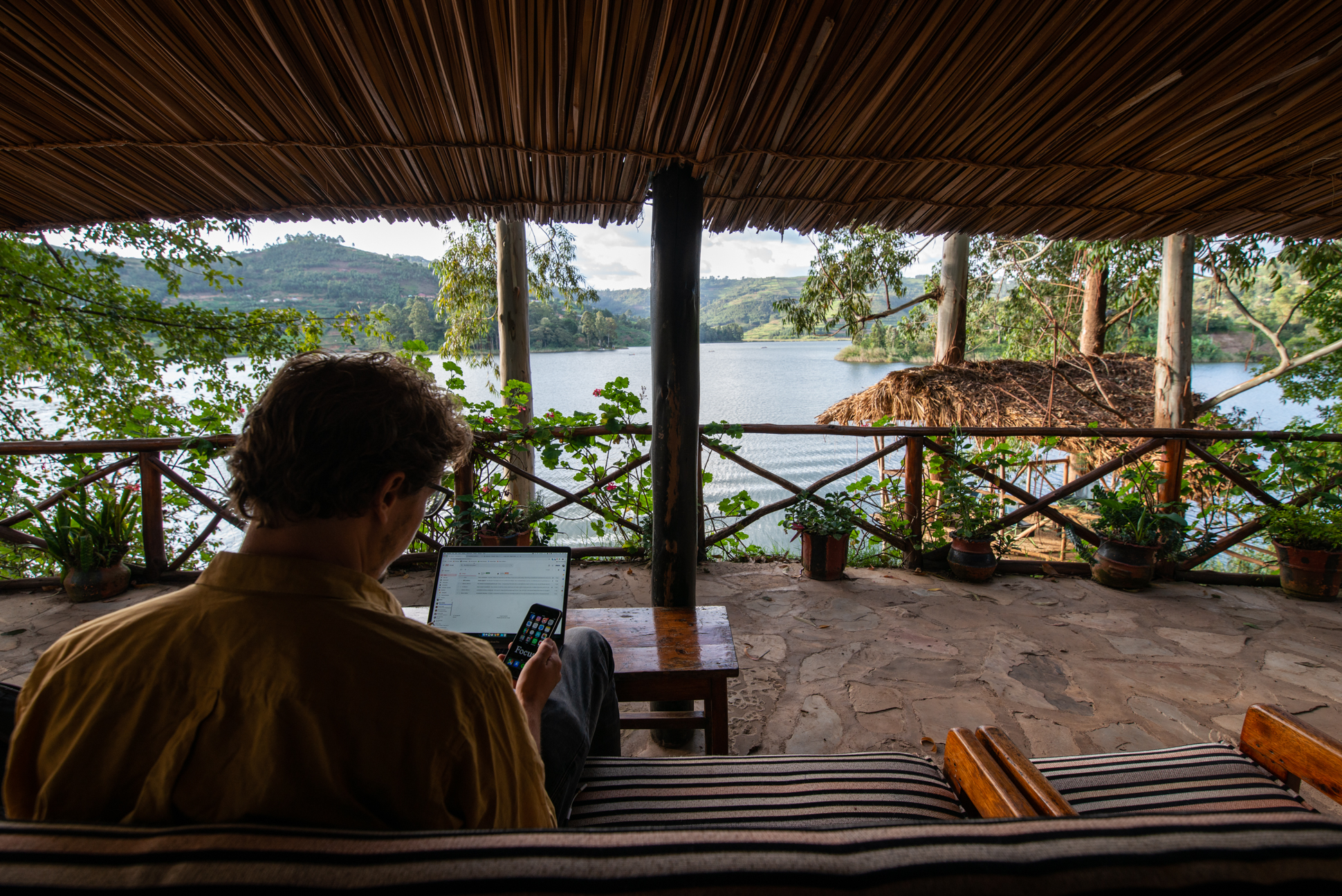 Digital Nomad at work at lake Bunyonyi with a lake view with islands and mountains. Ellis photography.