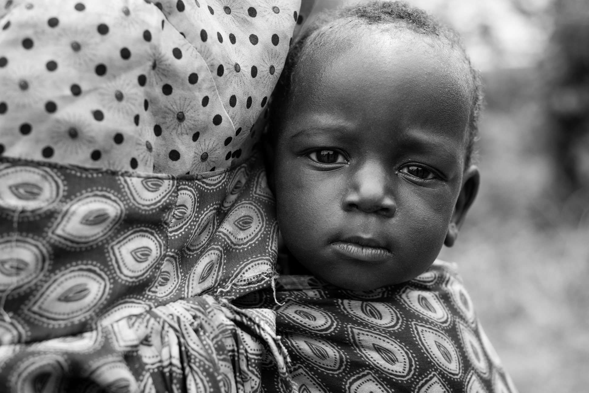 Portrait of an African baby in black and white. On the back of his mother. Made by Ellis Photography.
