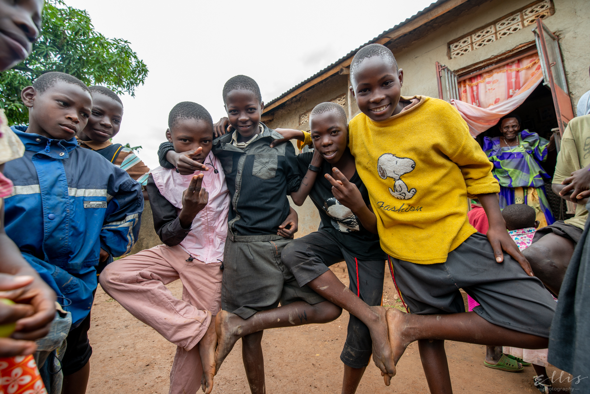 kids in Uganda smiling for the photograph. Great grandma on the background smiling.