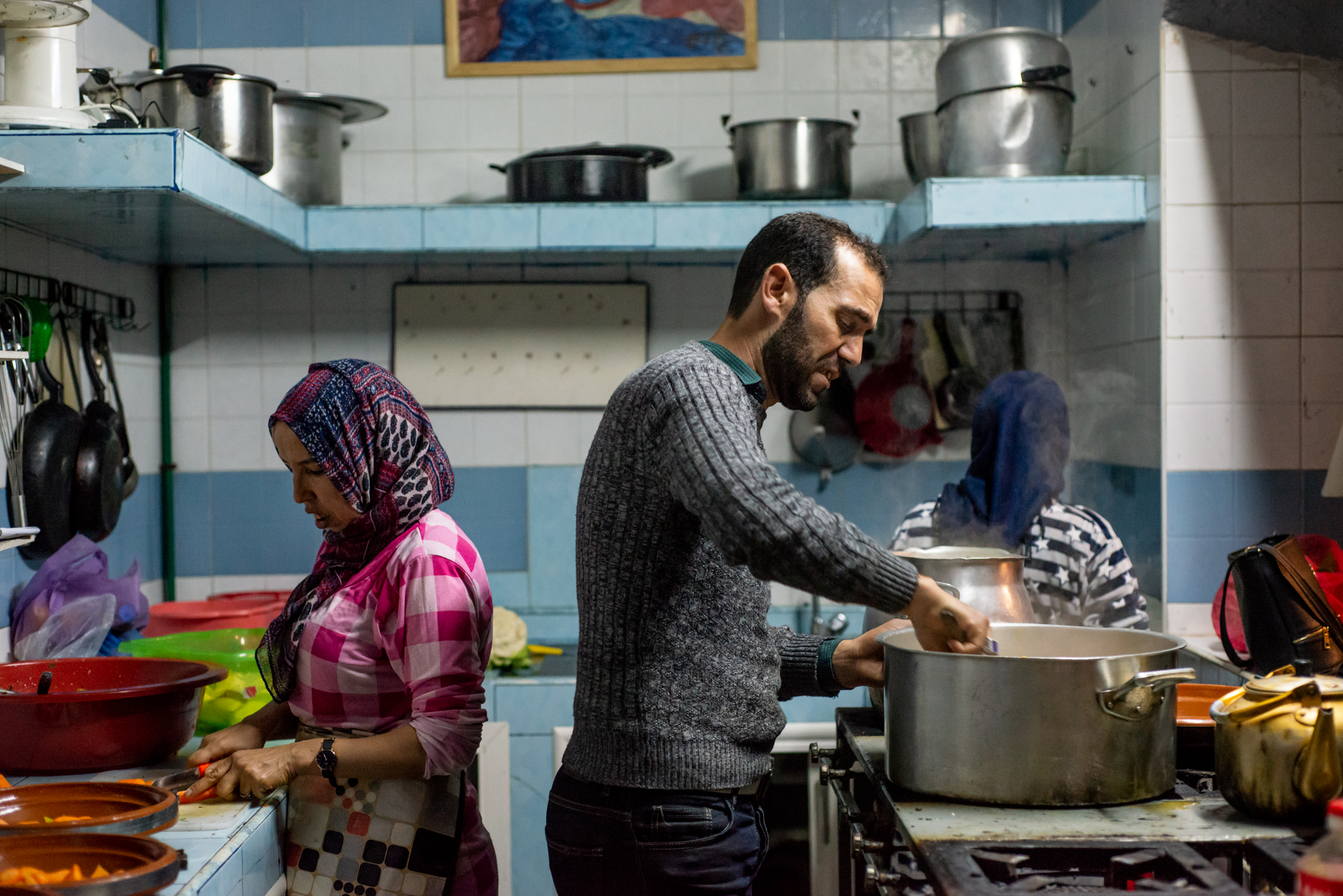 Daily life photography of a Moroccan man cooking in his kitchen with Tajine. Ellis Photography