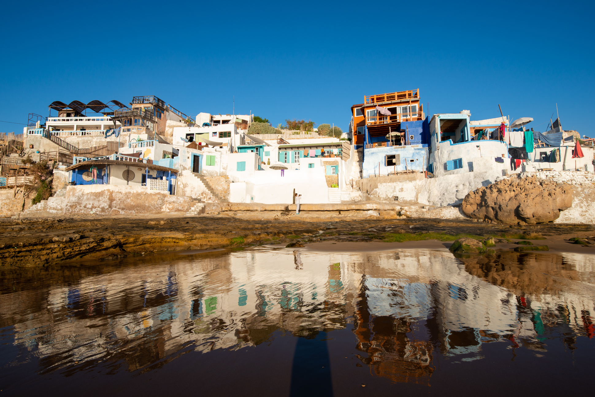 Beach houses reflecting in the ocean of Imsouane, Morocco, during sunset.