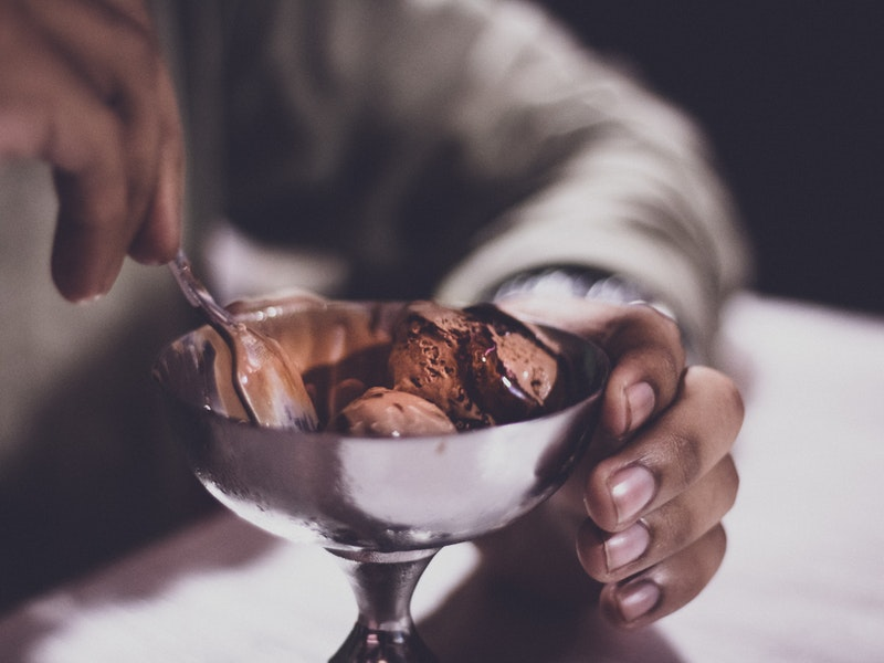 A man digs his spoon into a bowl of chocolate ice cream.