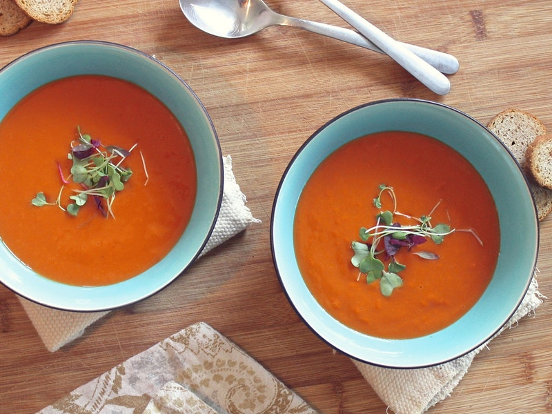 Two bowls of tomato soup, garnished with parsley, are shown here.