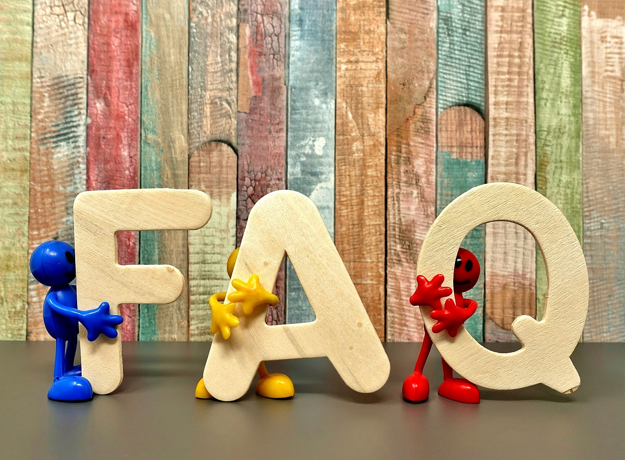 Three little figures -- one blue, one yellow, and one red -- each hold a wooden letter, F, A, and Q, respectively.