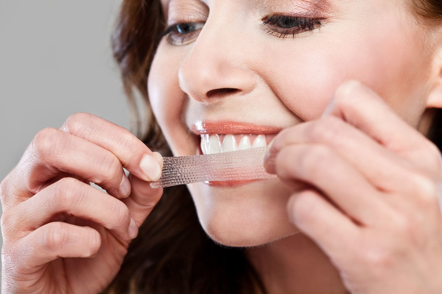 A woman prepares to place a whitening strip on her teeth.