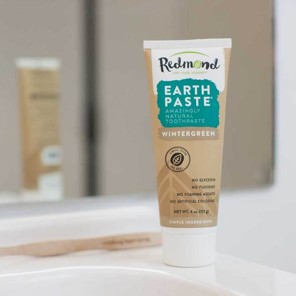 A brown tube of Redmond Wintergreen Earthpaste sits next to a toothbrush.