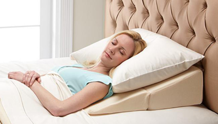A woman sleeps, using one pillow and a wedge-like pillow to elevate her head.