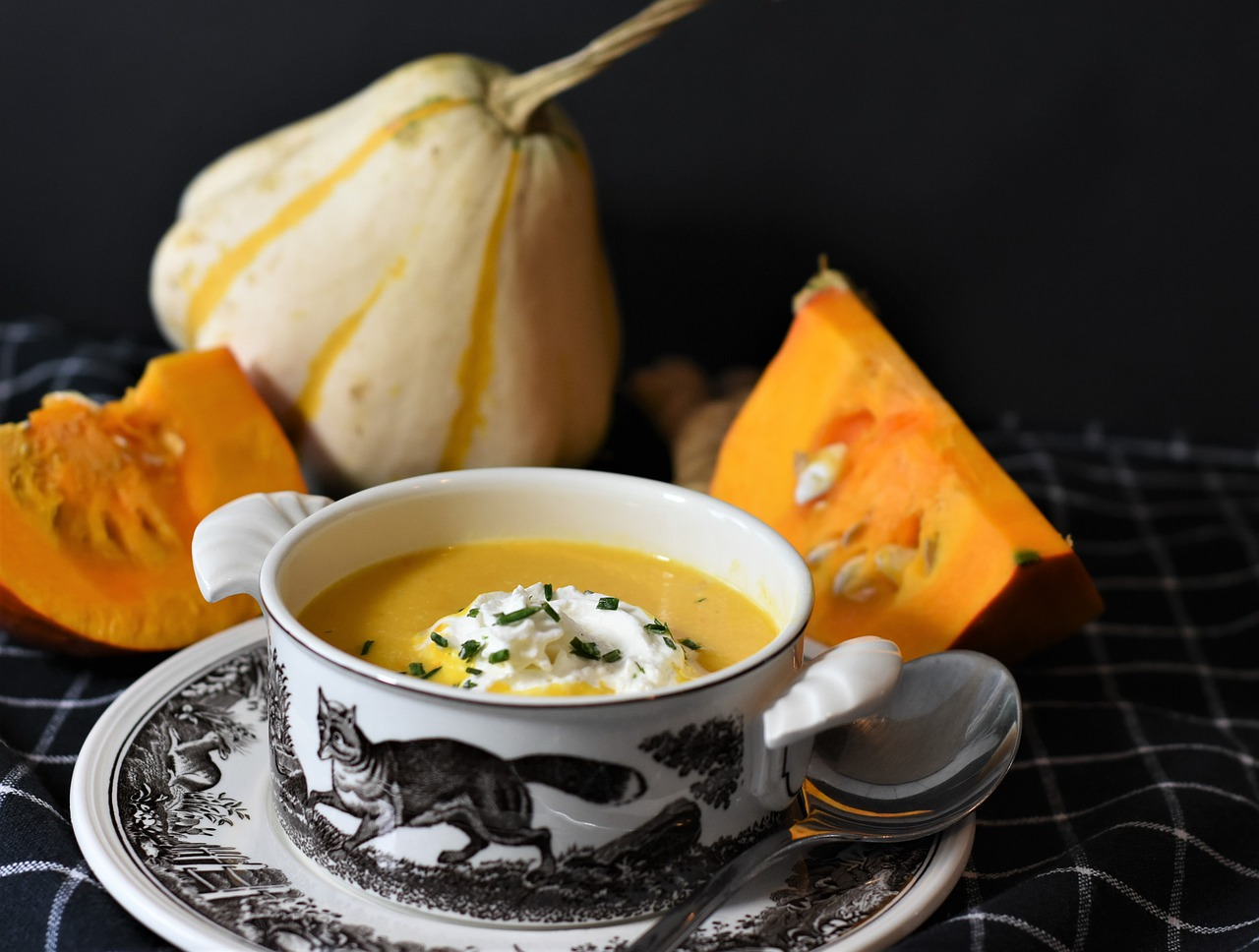 squash soup in a decorative ceramic bowl, with cream and chives dolloped in the middle. Squashes are arranged by the bowl.