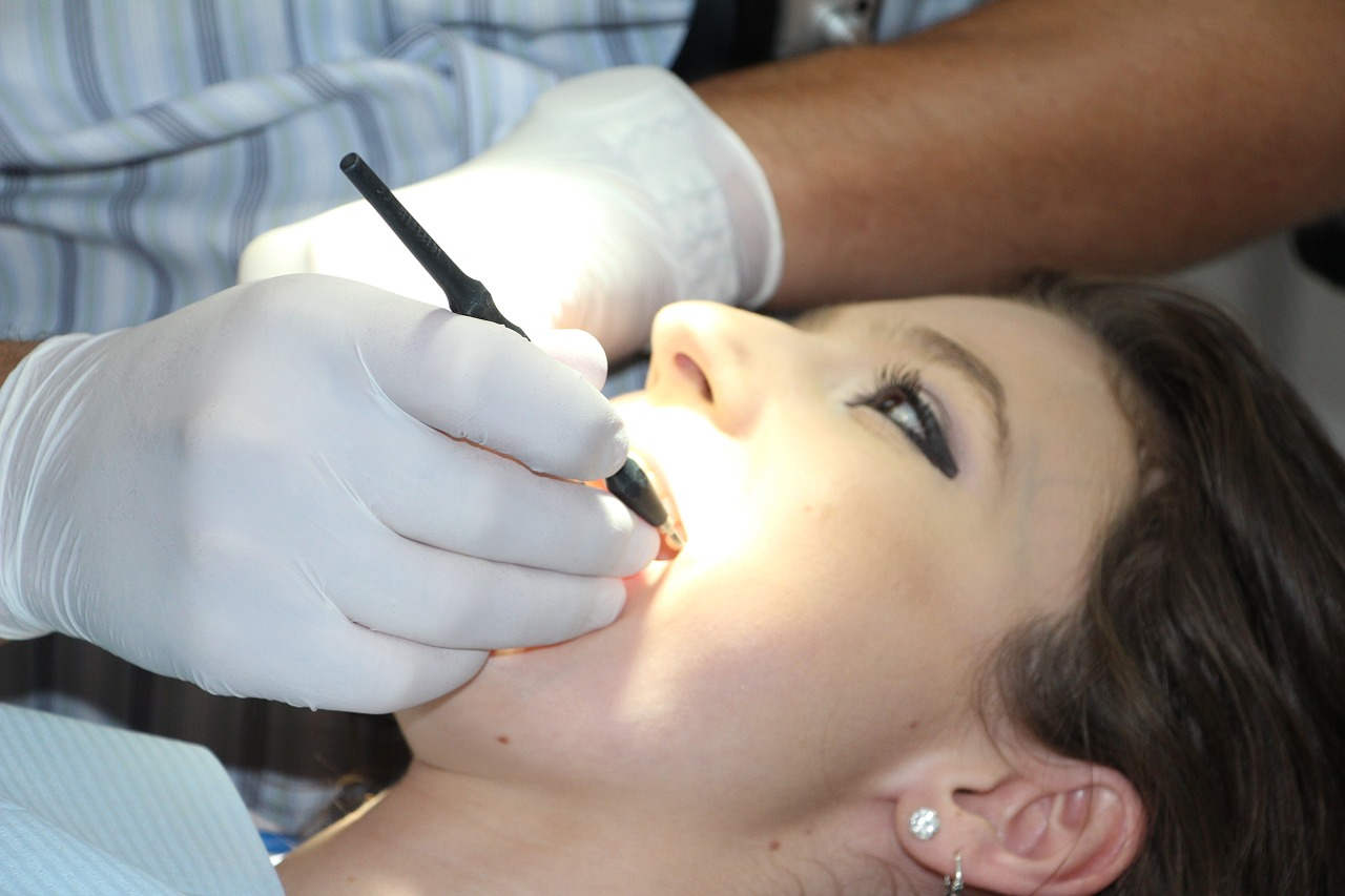 Woman lying down with dentist doing work inside her mouth