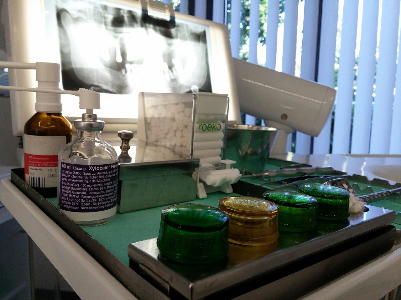 Dentist table filled with equipment, including an x-ray picture and cotton swabs
