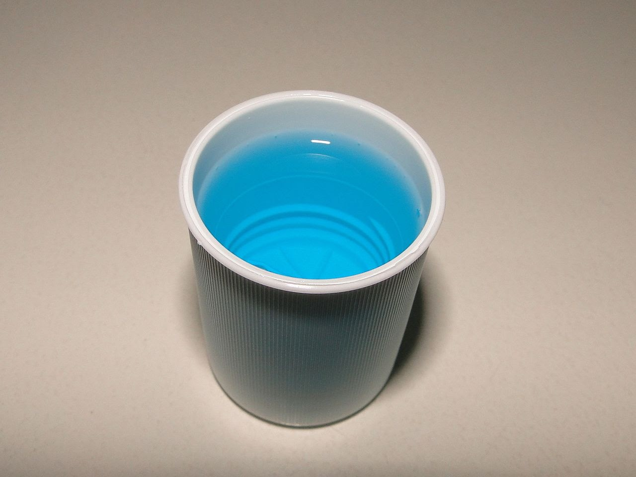 A cup of mouthwash sits waiting to be used.