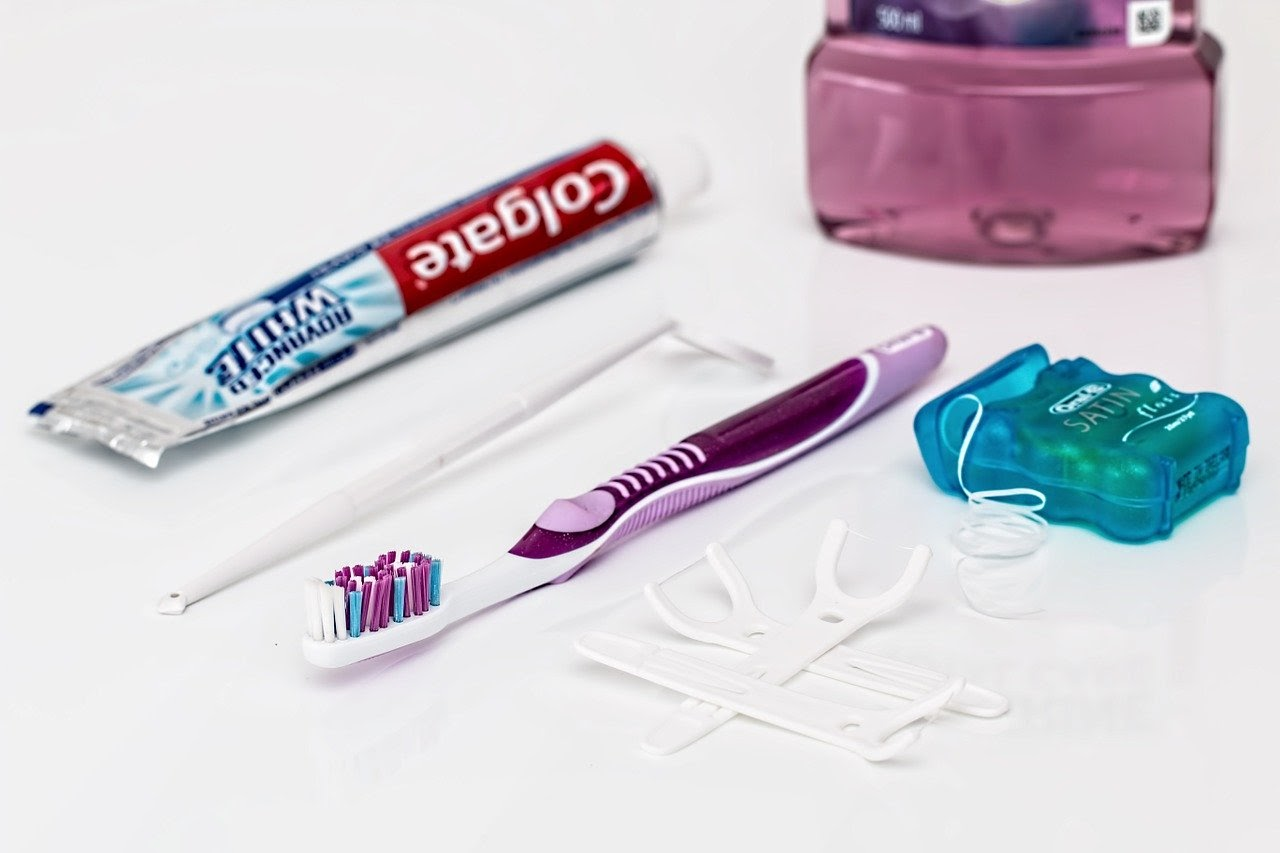 Toothpaste, mirror, toothbrush, floss, and mouthwash sit on a table.