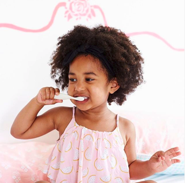 A little girl happily brushing her teeth with natural toothpaste.