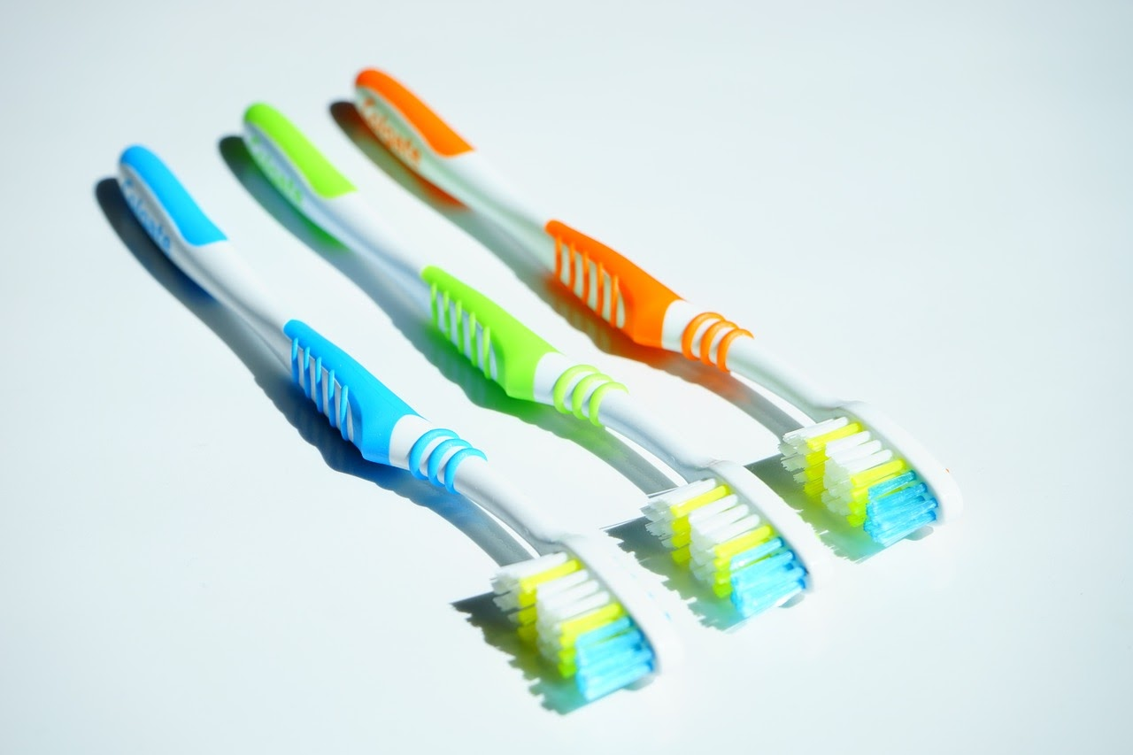 Three toothbrushes sit on a table.
