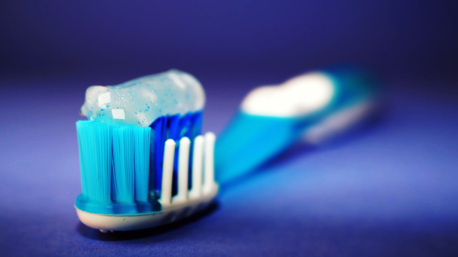 A toothbrush topped with sensitivity toothpaste sits waiting to be used.